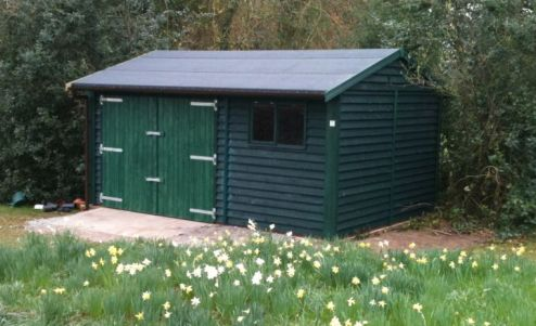 Sitting among the daffodils, this Warwick Buildings Workroom provides ideal storage for the lawn mower & other garden implements. Finished in Feather Edge Cladding & painted in Protek Spruce Green Wood Protector. Double Barn Style Doors replace the Standard Personal Door